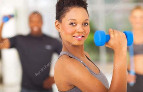 fit african woman lifting dumbbell