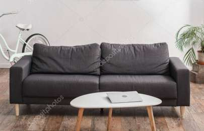 laptop on coffee table near grey couch and plant in modern apartment, banner