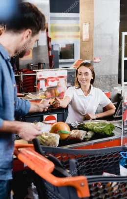 Smiling cashier taking credit card from customer near food on supermarket checkout