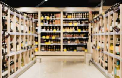 Blurred background of bottles on shelves in supermarket