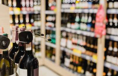 Close up view of wine bottles in supermarket on blurred background