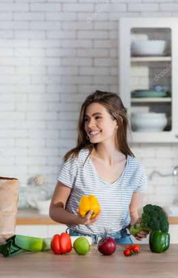 happy woman looking away while holding broccoli and bell pepper in kitchen