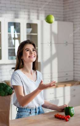 cheerful woman juggling with ripe apple near cherry tomatoes and bell pepper in kitchen