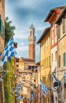 Walking in the picturesque streets in the medieval city centre of Siena, one of the nation\'s most visited tourist attractions i