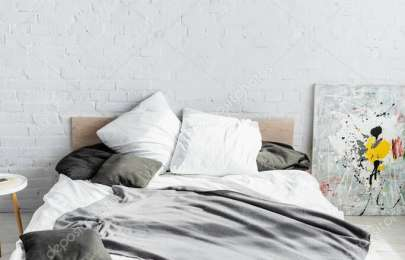 Grey blanket and pillows on bed at home