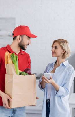 arabian man holding paper bag with fresh food near smiling woman with mobile phone