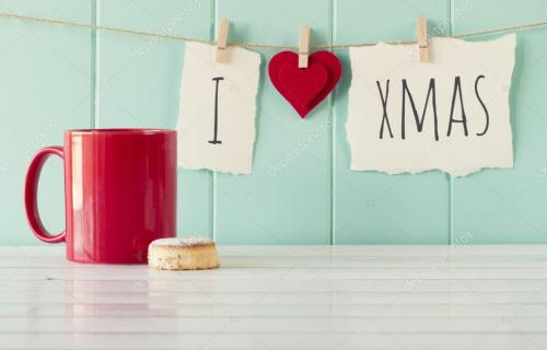 """I love xmas\"" hanging on a rope with clothespins. A robin egg blue wainscot as background and a red mug on a white wooden tabl"