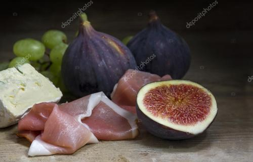 Figs with ham and cheese on rustic wood, food still life