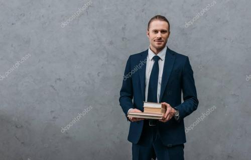young handsome businessman holding stack of books in front of concrete wall