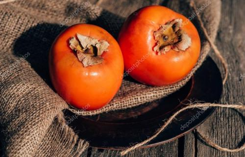 two delicious persimmons on sackcloth on wooden table