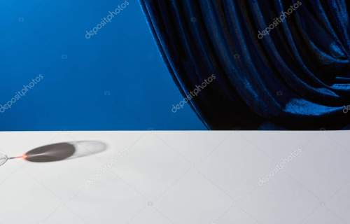 classic still life with shadow of wine glass on white table near velour curtain isolated on blue
