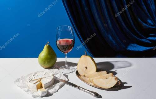 classic still life with pears, red wine and Camembert cheese on white table near velour curtain isolated on blue