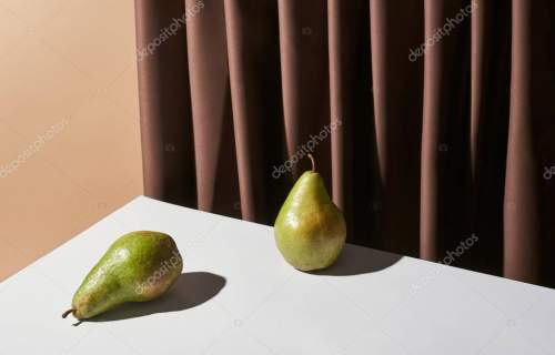 classic still life with pears on table near curtain isolated on beige