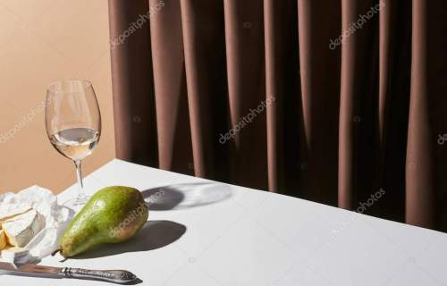 classic still life with Camembert cheese, white wine and pear on table near curtain isolated on beige
