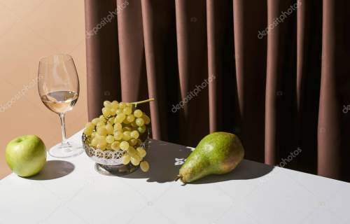 classic still life with white wine and fruits on table near curtain isolated on beige