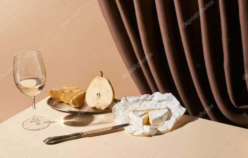 classic still life with pear, white wine and Camembert cheese on table near curtain isolated on beige