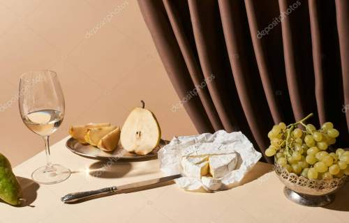 classic still life with pears, grape, white wine and Camembert cheese on table near curtain isolated on beige