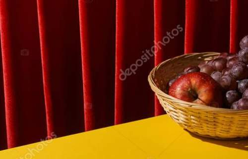 classic still life with fruits in wicker basket on yellow table near red curtain, panoramic shot