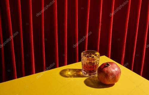 classic still life with pomegranate near glass of red wine on yellow table near red curtain