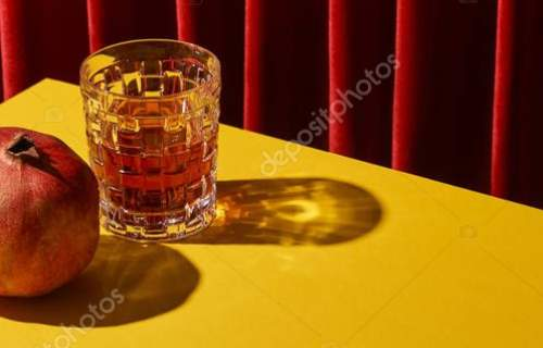 classic still life with pomegranate near glass of red wine on yellow table near red curtain, panoramic shot