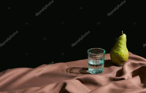 classic still life with pear and water in glass on table with brown tablecloth isolated on black