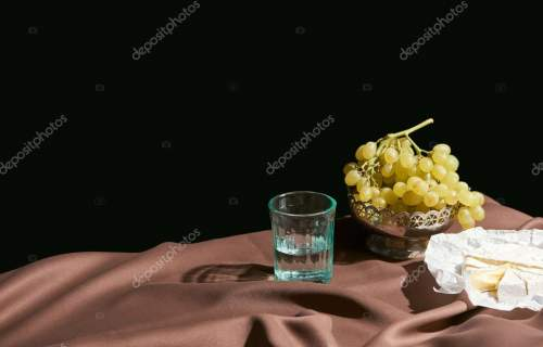 classic still life with Camembert cheese, grape and water in glass on table with brown tablecloth isolated on black