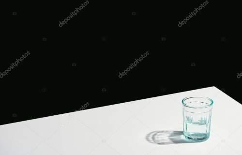 classic still life with water in glass on white table isolated on black