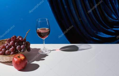 classic still life with fruits, red wine on white table near velour curtain isolated on blue