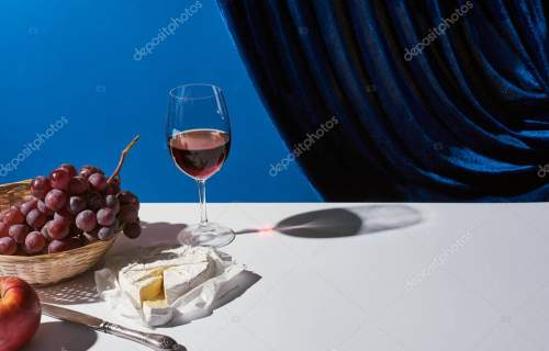 classic still life with fruits, red wine and Camembert cheese on white table near velour curtain isolated on blue