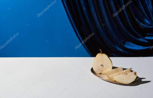 classic still life with pear on silver plate on white table near velour curtain isolated on blue