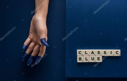 cropped view of woman with painted fingers near classic blue lettering on cubes on blue background