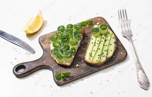 fresh cucumber toasts on wooden cutting board near cutlery and lemon on white background