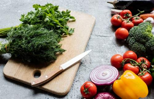 colorful fresh ripe vegetables near cutting board with knife on grey concrete surface