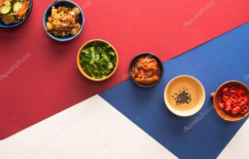 top view of bowls with korean side dishes and oil on blue, crimson and white