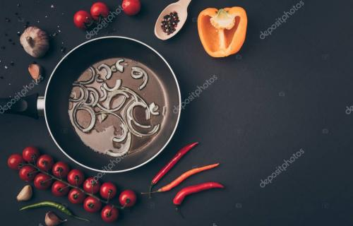 top view of frying pan with onion and oil among vegetables on gray table