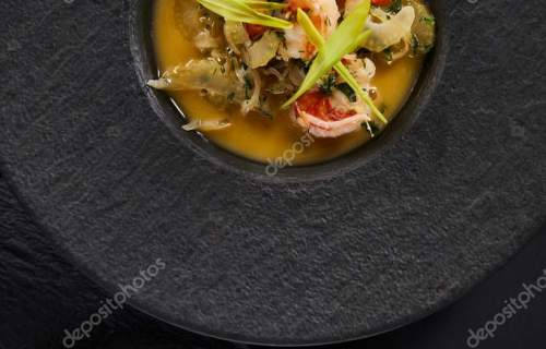 top view of delicious restaurant soup with shrimps in black plate with cutlery
