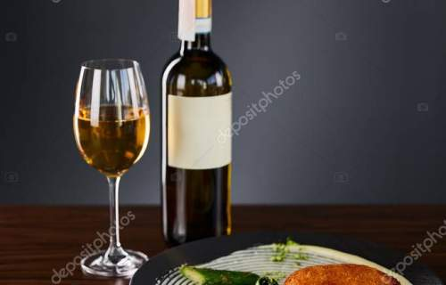 delicious chicken kiev and mashed potato served on plate near cutlery and white wine on black background