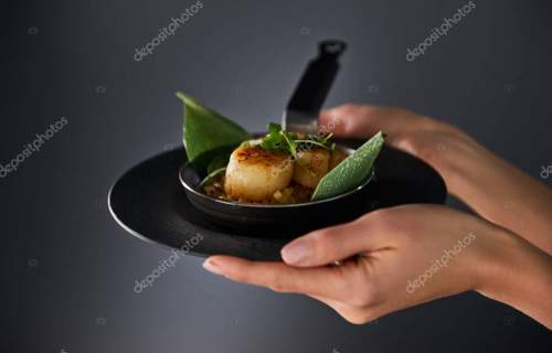 cropped view of woman holding plate with delicious grilled scallops on black background