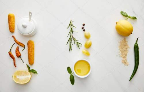 Top view of olive oil, gravy boat with vegetables and herbs on marble background