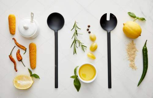 Top view of kitchenware, vegetables and herbs on marble background