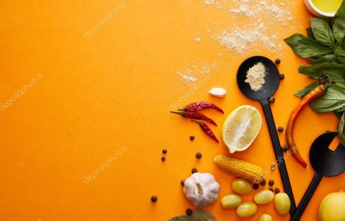 Top view of organic vegetables with basil and spices on orange background