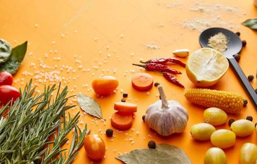 Fresh rosemary with vegetables and spices on orange background