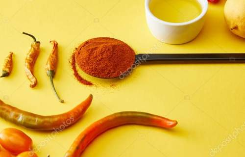 Chili peppers with vegetables and olive oil on yellow background