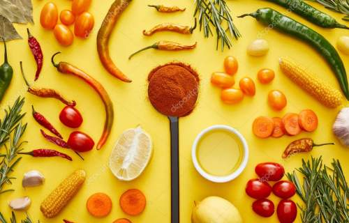 Top view of organic vegetables and herbs with chili spice on yellow background