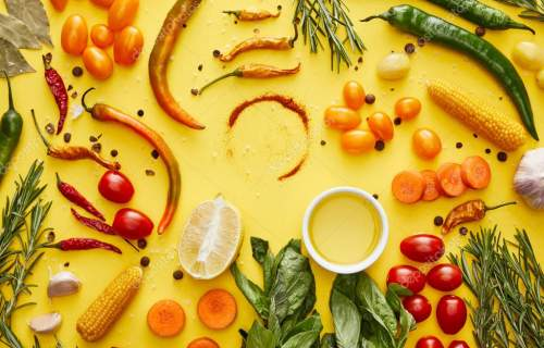 Top view of organic vegetables and fresh herbs with spices on yellow background
