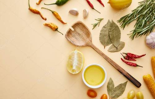 Top view of wooden spoon with spices and vegetables on beige background