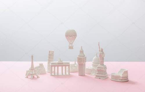 small figurines from different countries on grey and pink