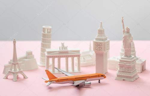 toy airplane near small statuettes of different countries on grey and pink