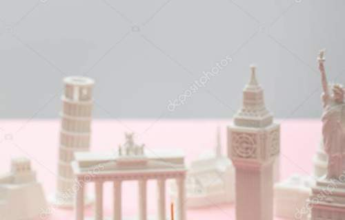 selective focus of toy airplane near small statuettes of different countries on grey and pink