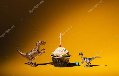 Toy dinosaurs with party cap beside cupcake with candle on orange background